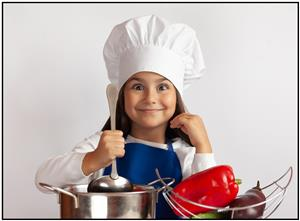 Young girl in chef hat with kitchen utensils